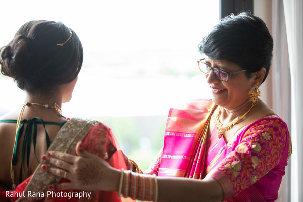 Indian bride being assisted by her mother