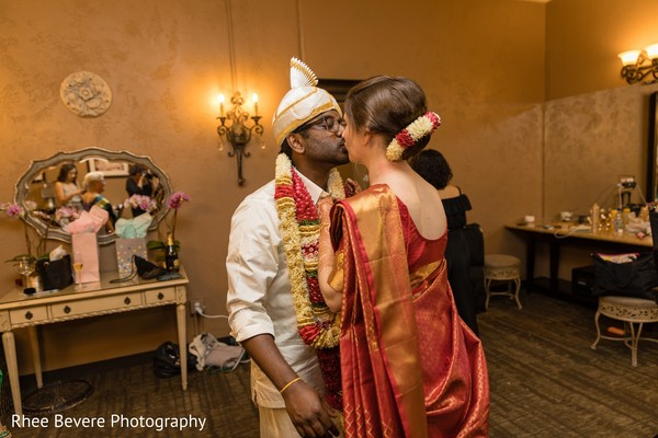 Lovely Indian bride giving kiss to groom.