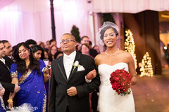 Glamorous Indian bride walking in with parent.