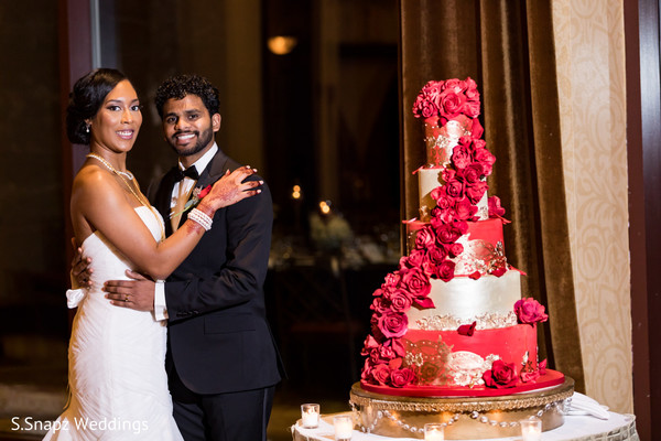 Lovely capture Indian bride and groom next to cake.
