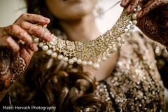 Indian bride putting her Polki necklace choker.