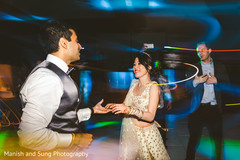 Indian bride dancing with Indian groom at reception