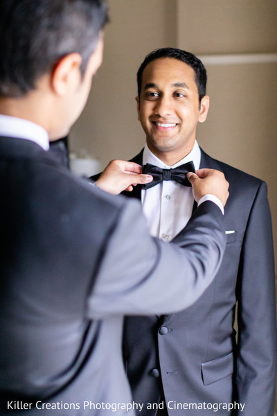 Indian groom being assisted with wardrobe