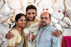Indian groom posing with his parents