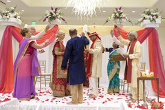 Indian wedding parents throwing rose petals at ceremony.