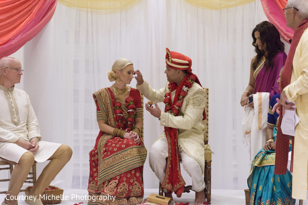 Indian lovebirds putting marks on forehead for protection.