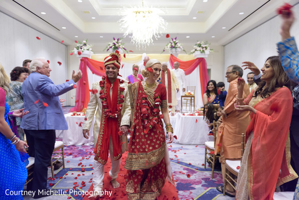 Joyful Indian bride and groom walking out from wedding ceremony.