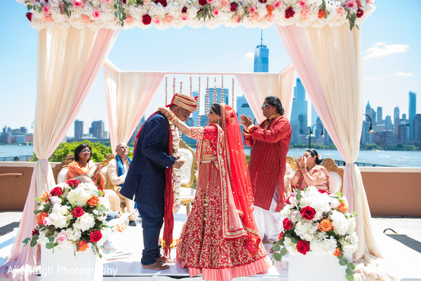 Indian bride  putting flower garland to groom.