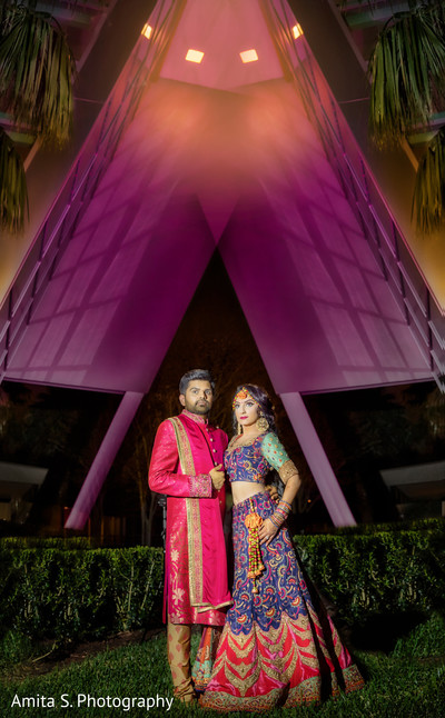 Indian bride and groom posing with their sangeet outfits.