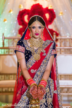 Beautiful Indian bride showing her jewelry and henna art.
