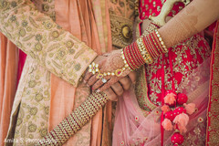 Stunning closeup capture of indian bride and grooms holding hands.