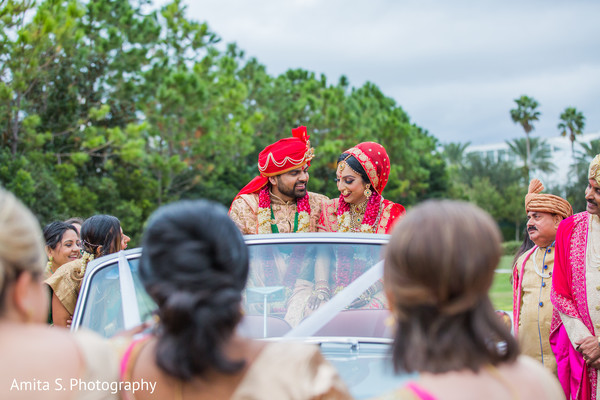 Joyful Indian bride and groom about to leave from ceremony.