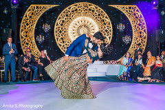 Indian bride and groom looking at each other while  dance.