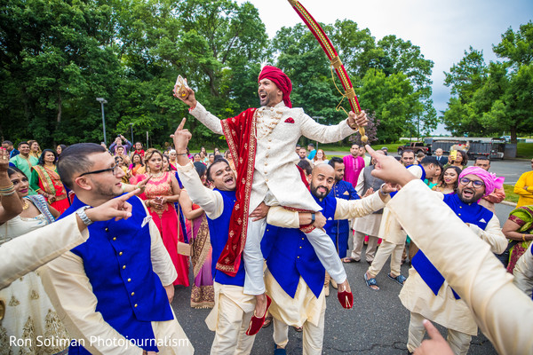 Indian groom being lifted by Indian groomsmen at baraat.