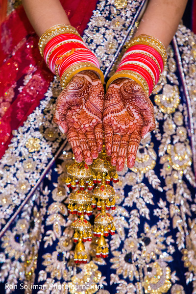 Lovely Indian bride showing her henna art on her hands.