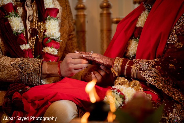 Indian groom putting the ring to bride during the ceremony ritual.