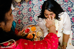 Indian bride getting the turmeric paste on her face.