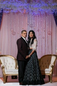 Indian newlyweds posing with their reception attires