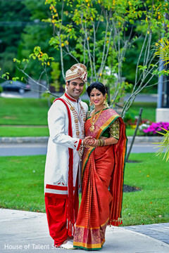 Indian bride and groom outdoors on their wedding ceremony outfits.
