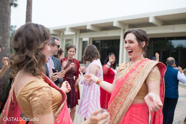 Joyful Indian bridesmaids at baraat procession capture.