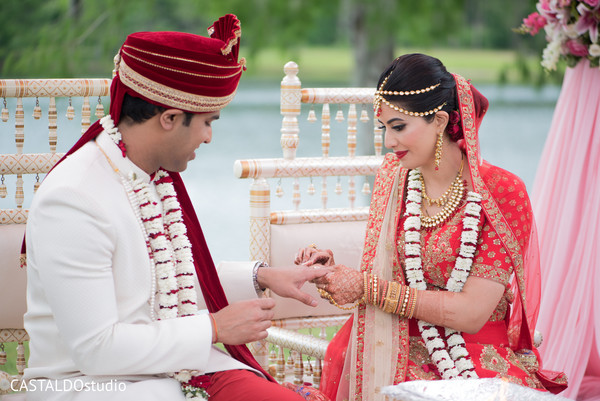 Indian bride putting ring to Indian groom.
