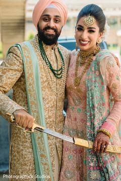 Indian bride and groom holding the kirpan