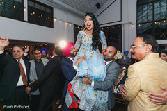 Indian bride being lifted up by groomsmen.