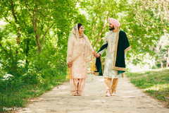 Dazzling Indian bride and groom walking holding hands.
