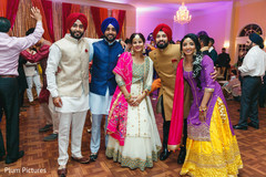 Elegant Indian bride and groom with relatives capture.