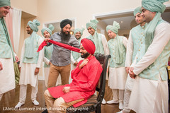 Indian groom being helped to get his turban on.