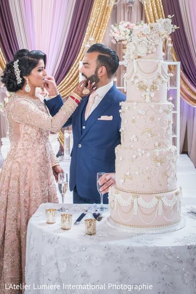 Lovely capture Indian bride and groom eating cake together.