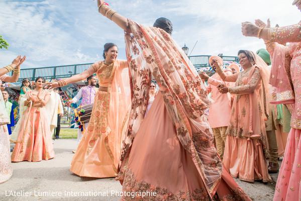 Indian bridesmaids dance at baraat celebration.