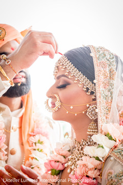 Red mark applied on bride's forehead by groom.