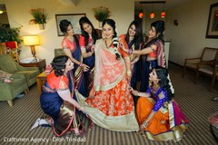 Bridesmaids assisting the Indian bride