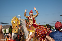 Indian groom riding the horse during the Baraat
