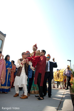 Indian groom being lifted by special guests during the baraat