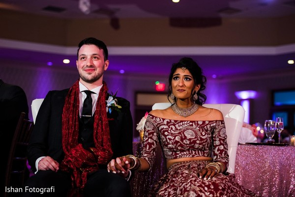 Indian bride and groom holding hands at the reception
