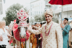 Indian groom posing with the horse during the Baraat