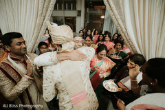 Indian groom being greeted by guests