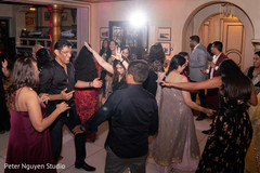 Vibrant indian pre wedding guests dance capture.