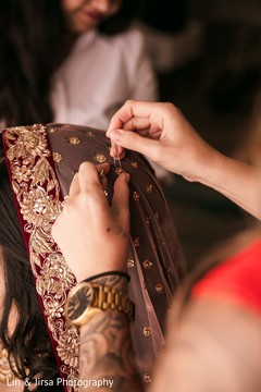 Indian bride getting help to put her wedding Ghoonghat veil on.