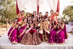 Indian bride, groom and bridesmaids looking at camera.