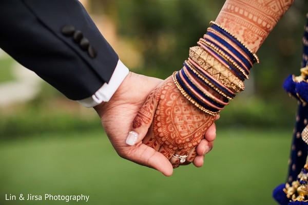 Indian couple walking holding hands closeup.