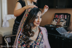 Indian bride being assisted with hair and makeup