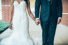 Joyful Indian  bride and groom holding hands capture.
