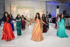 Joyful Indian bride and bridesmaids at reception dance performance.