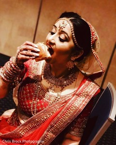 Lovely Indian bride taking a bite capture.