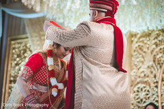 Indian groom putting garland to bride capture.