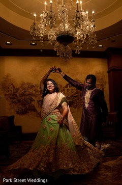 Indian bride and groom  celebrating sangeet with a dance.