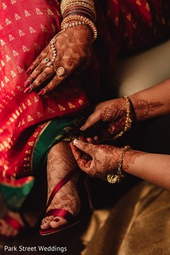 Indian bride being helped by putting her anklets.